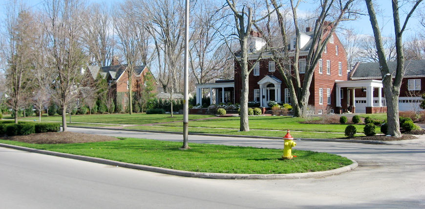 A median in front of a large home in a residential neighborhood