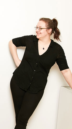 A laughing woman in black clothing leans casually against a plinth.