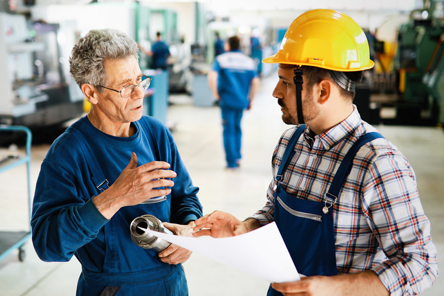 An older metal-worker in blue holds a part and discusses data with a hard-hat supervisor
