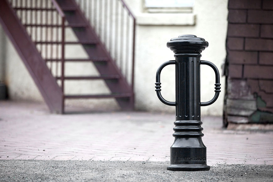 A traditional bollard with bike locking arms sits behind a building for employee use