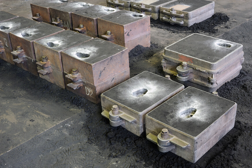 Green sand molds on a foundry floor prepared for casting