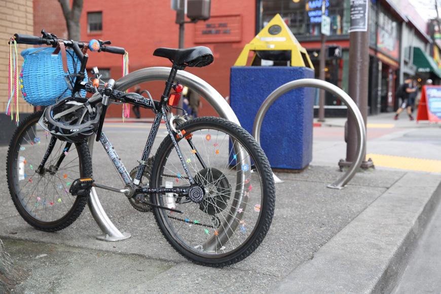 Una bicicleta decorativa está asegurada a un cicloestacionamiento tanto con el candado de cadena como con el candado en U