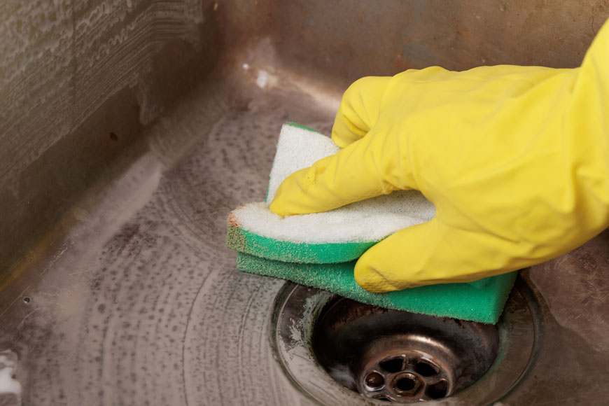 Close-up of hand in yellow rubber glove cleaning an old stainless sink with a mild abrasive