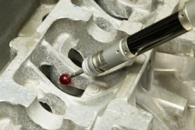 A CMM probe topped with a red bead measures an aluminum casting