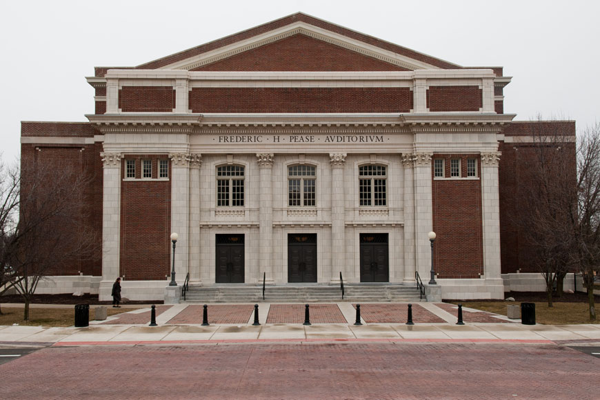 Small black pawn like bollards protect the front of a brick and stone auditorium