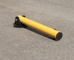 A collapsible yellow bollard is folded flat against the concrete