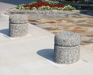 Short concrete bollards with decorative pebble surfaces complement a stone walkway