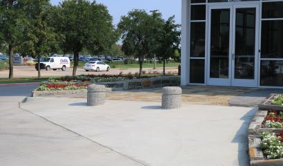 Two short concrete bollards help prevent cars from coming too close to the main door of a building