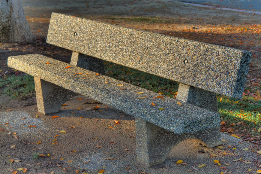 A concrete park bench is finished with pebbles.