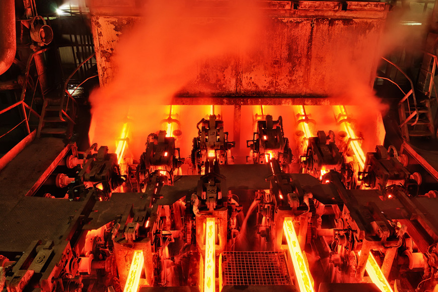 Glowing bars of steel are extruded from a continuous metal casting machine