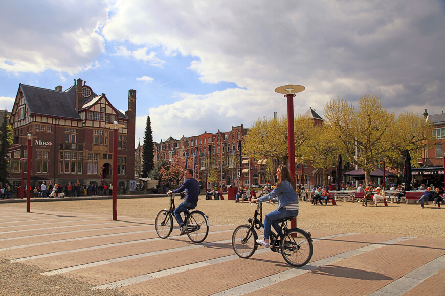 Man and woman on bicycles reveals Amsterdam's bike culture in historical center