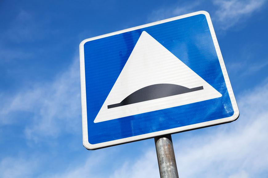 panneau de signalisation carré d'un dos d'âne devant un ciel bleu