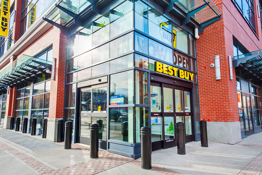 A series of thick black bollards protect the windows of a Best Buy