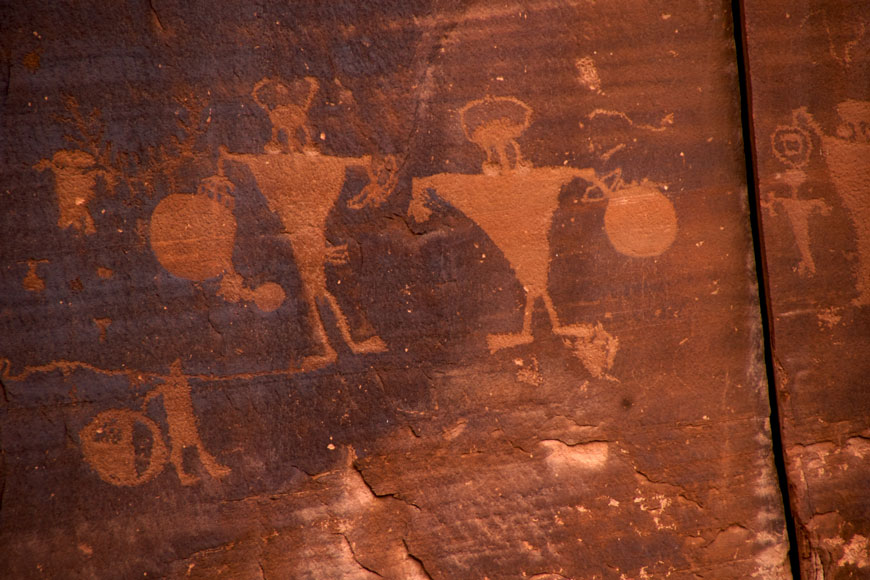 On a dark red clay wall, two images of two warriors with spears and horns are scratched into the surface