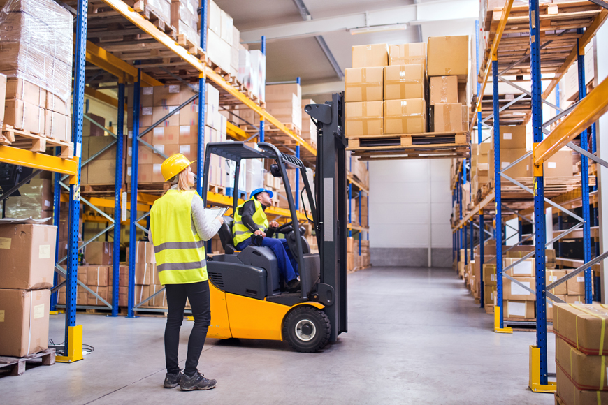 A worker carefully operates a forklift while a supervisor looks on, both wear hardhats