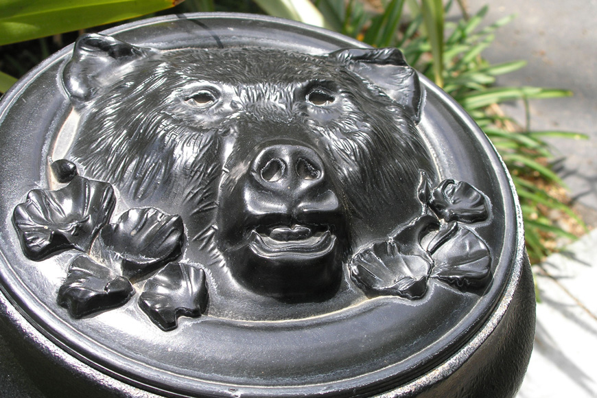 The top of a bollard is customized with a bear's head and flowers