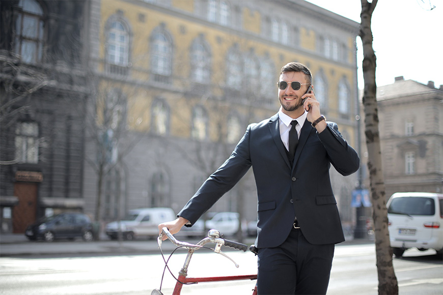 Smiling gentleman leaning on his bicycle outside of work