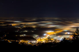 A picture of a town's lights through fog from up a hill
