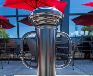 A decorative bike parking bollard edges the patio of a café