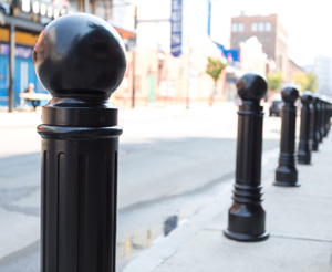 Slim black architectural bollards with fluted sides protect a sidewalk