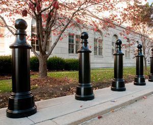 Tall black architectural bollards with tapered bodies and ball caps enhance a building front