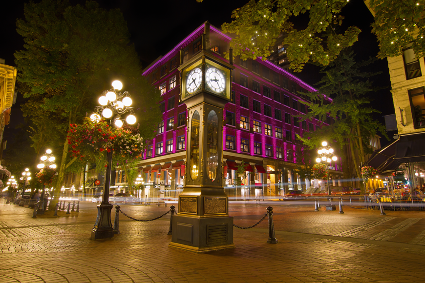 A glowing night scene features a vintage steam clock on a cobblestone street with a purple-lit building behind it