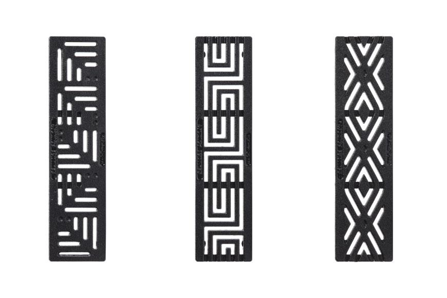 Three studio shots of decorative grates featuring angular slot patterns, painted black.