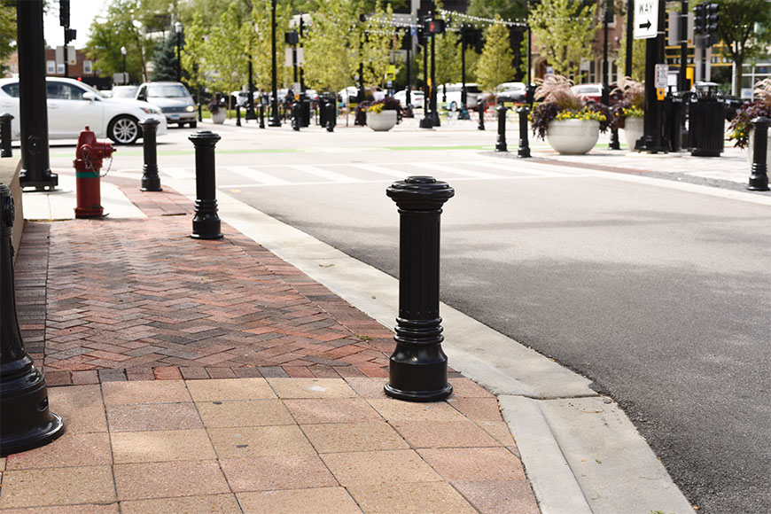 Traditional bollards placed along sidewalk to steer away vehicles