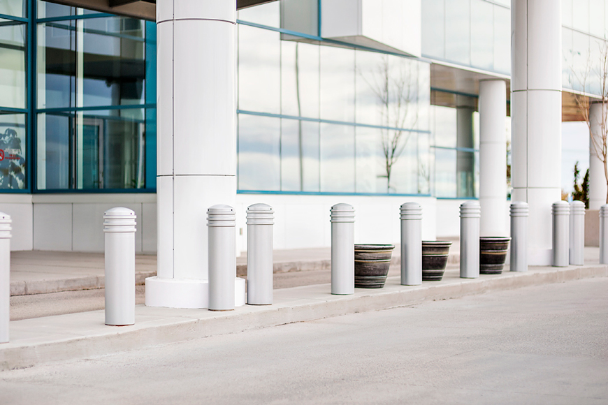 White bollards blend in with a white and glass building