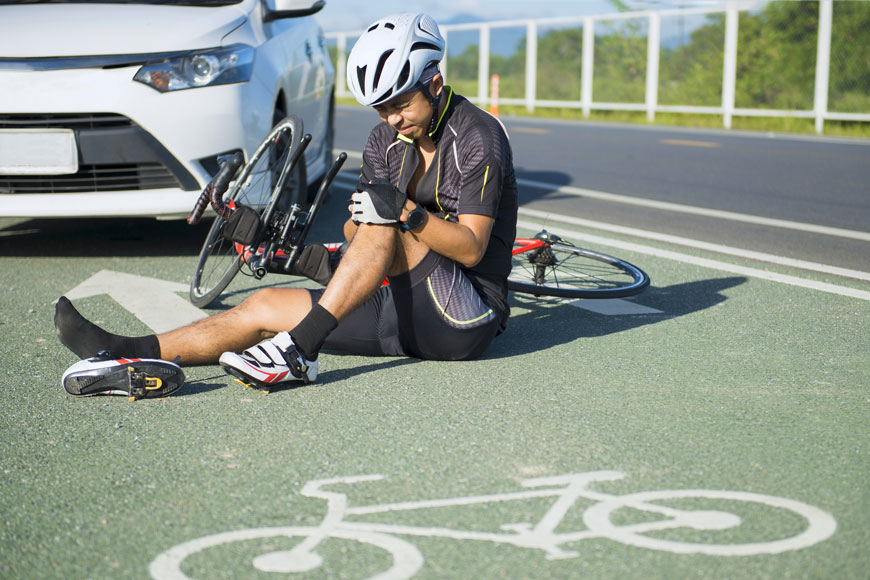 An injured cyclist sits on the ground in a separated bike line after an accident
