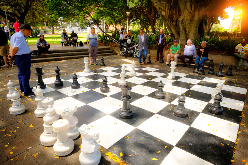 People stand and sit around a giant chess board in a park while older men play chess