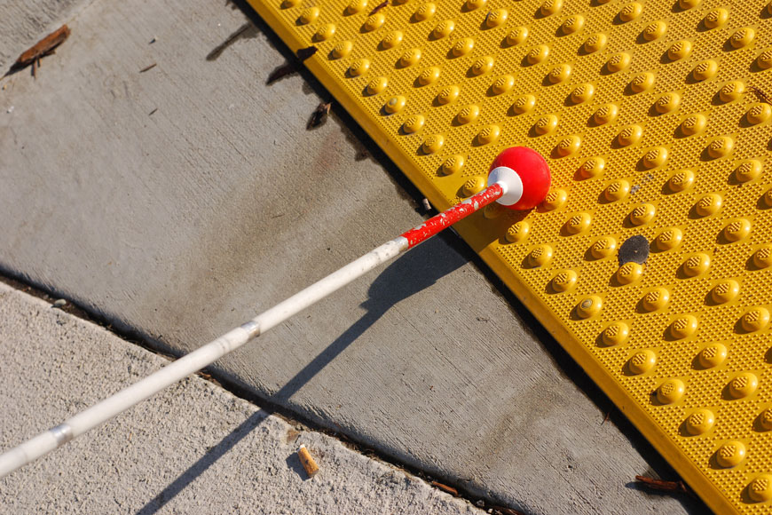 A white cane sweeps across a bright yellow cast iron detectable warning plate