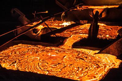 Glowing liquid titanium has dark slag floating on its surface