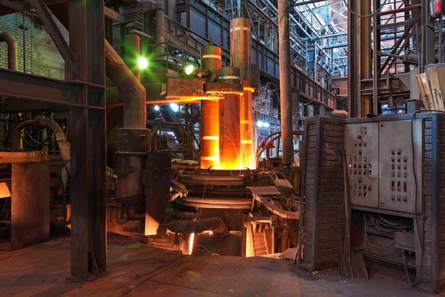 Metal being melted in an electric arc furnace inside a foundry