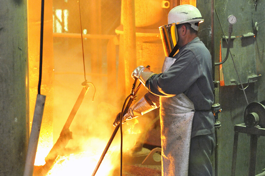 Un travailleur testant la température du métal portant un vêtement de fonderie de sécurité
