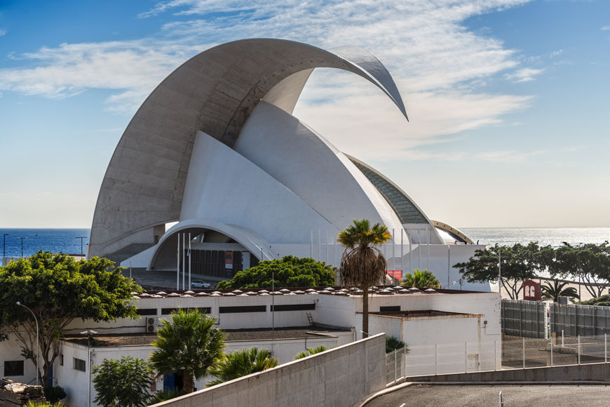 A curl of concrete, like an arching leaf, curls several stories over white concert hall with many asymmetrical layers