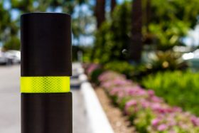 A black bollard with yellow reflective tape stands before a very blue sky