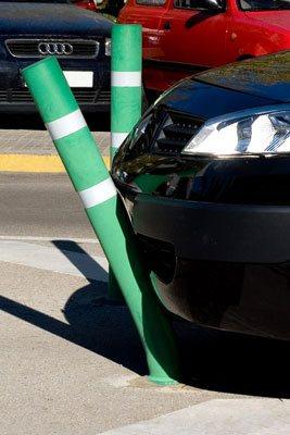 A green flexible bollard bends under the bumper of a black car
