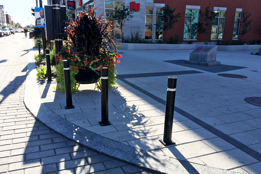 Three polyurethane black bollards protect pedestrian space
