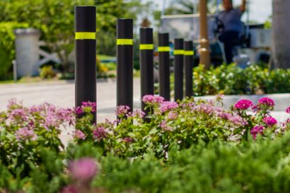 A series of flexible bollards separates a parking lot from the main buildings