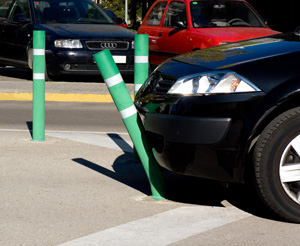 A green flexible bollard bends out of the way of an incoming black vehicle