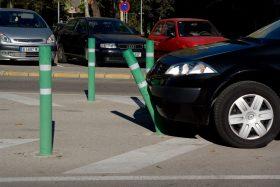 A green bollard bends as it is nudged by a black car in a parking lot