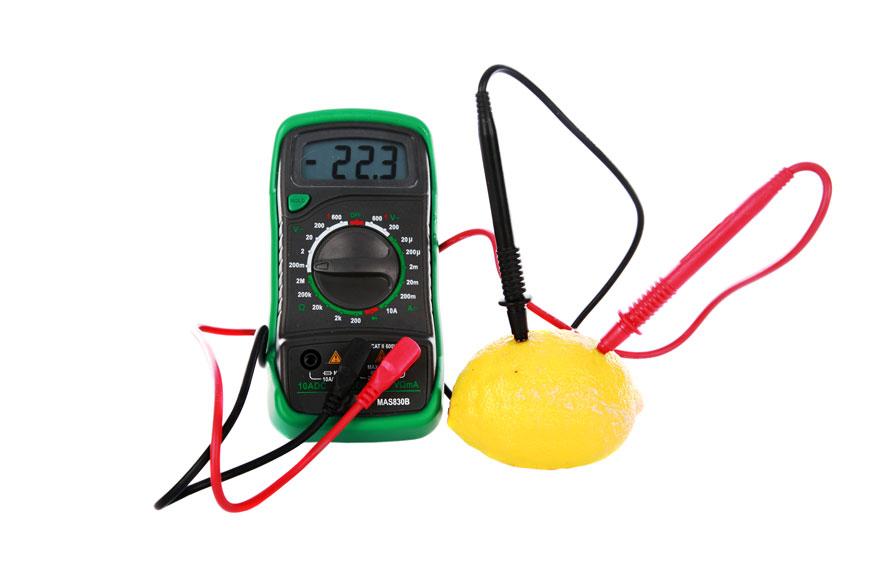 A multimeter measures electricity through a lemon