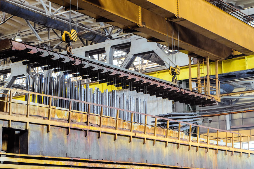 Two pulleys on a crane ready to lower a steel grid with rows of rods hanging to be dipped into molten zinc