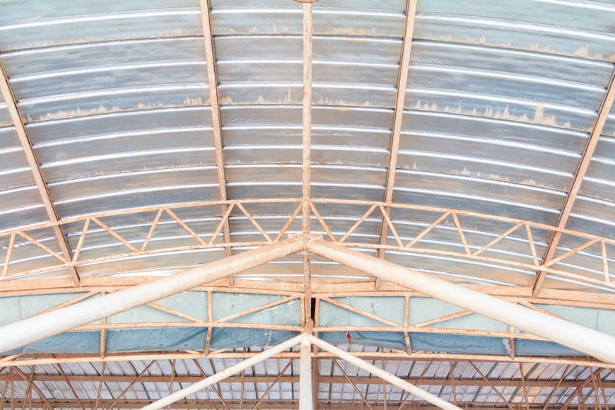The galvanized metal roof of a building shows white rust where moisture has collected