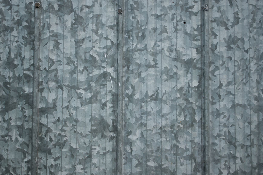 A sheet of galvanized steel is covered in large leaf-like spangles of dark grey, light grey, and silver