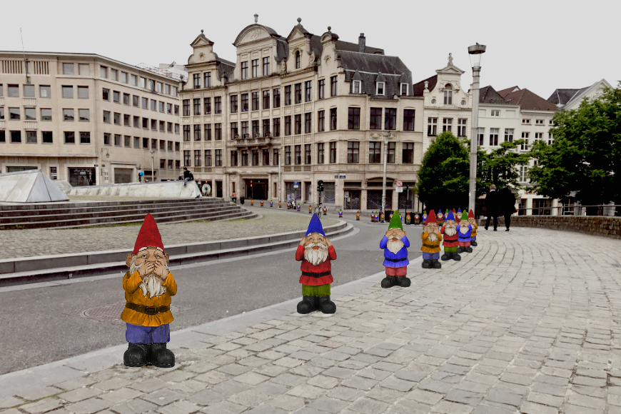 A variety of colorful gnomes stretch along the curb of a traditional European streetscape