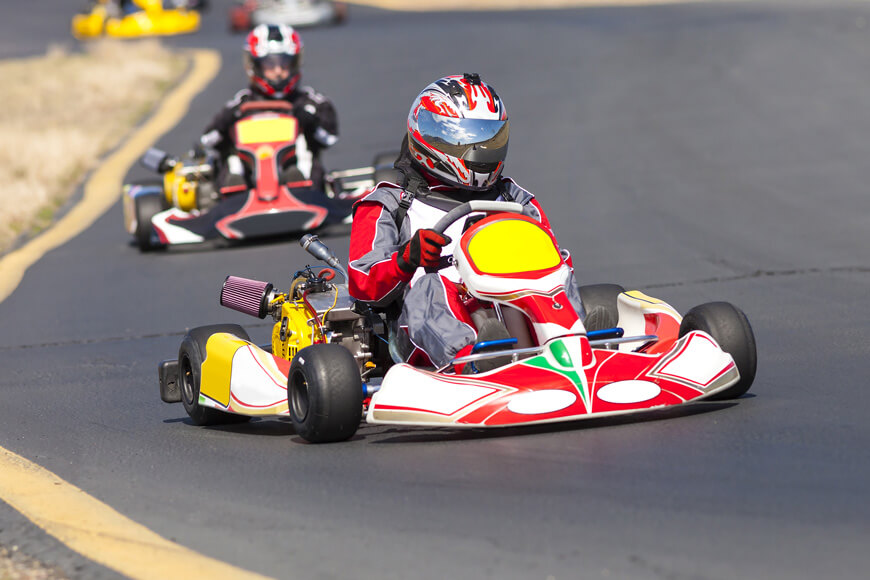 Go-kart racers are racing past the corner of the race track