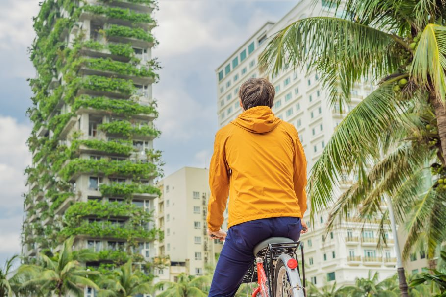 A man on a bike looks up at a skyscraper that has greenery on its cladding