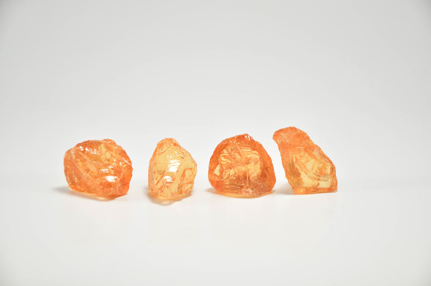 Four pebbles of rosin with an amber glow sit on a white background